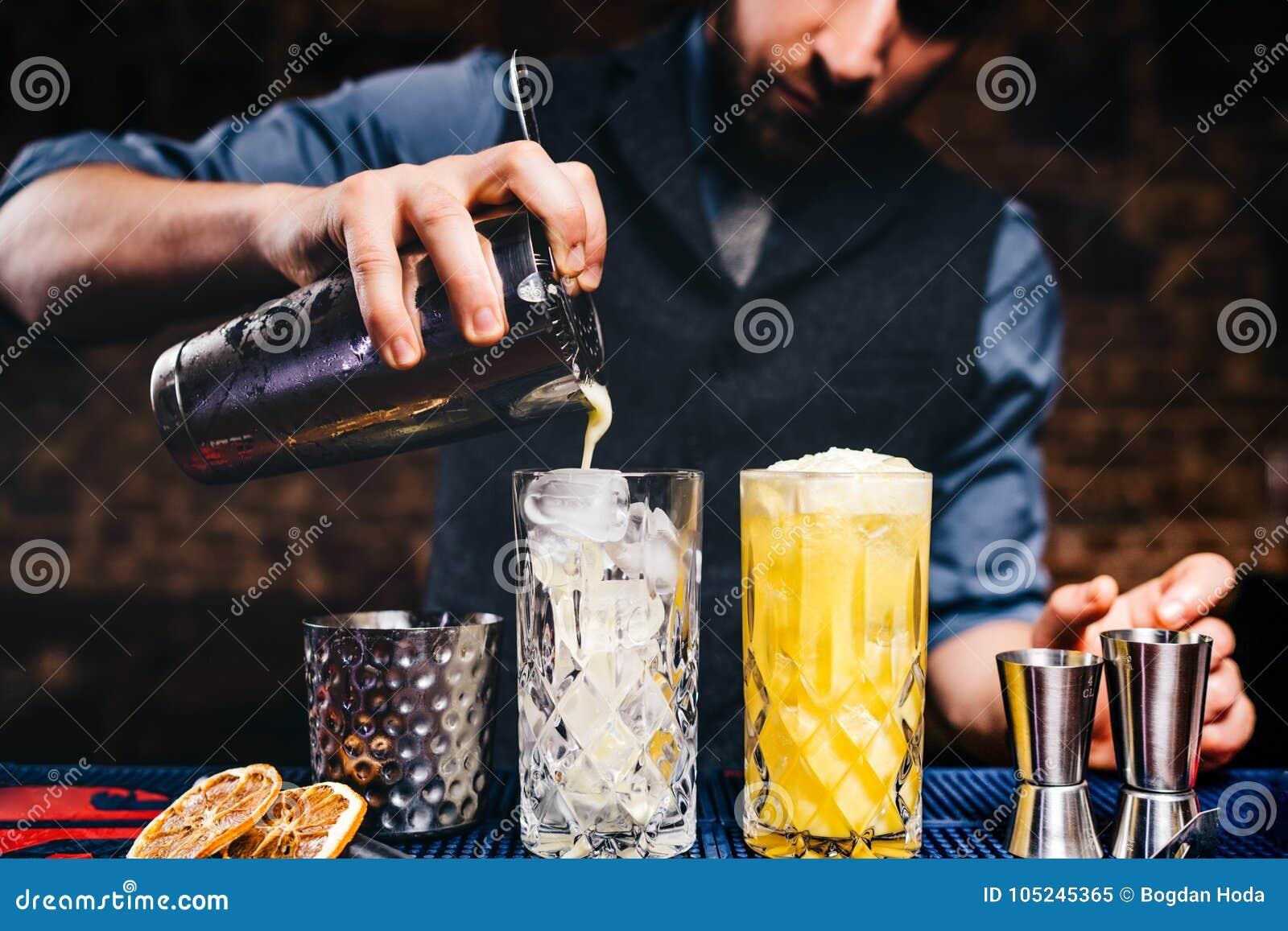 Tappningbartender som häller den nya orange vodkacoctailen över is i crystal glasföremål