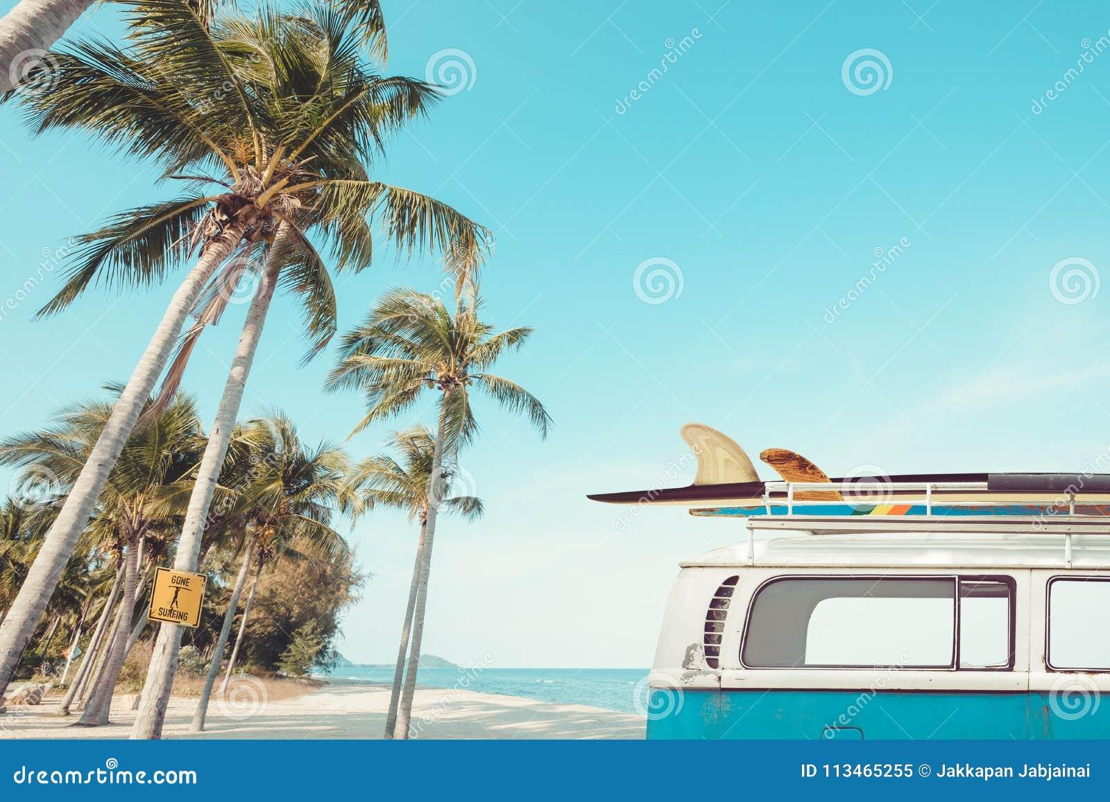 Tappningbil som parkeras på den tropiska strandsjösidan med en surfingbräda på taket