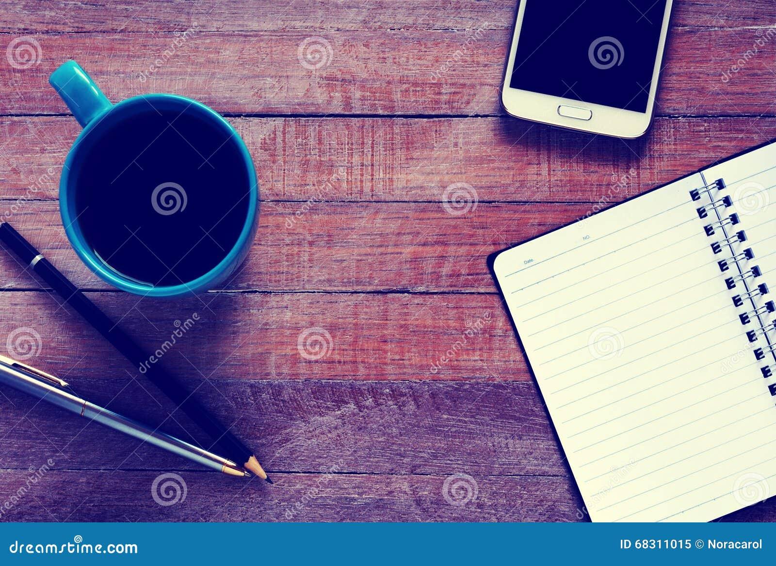 Tappningfoto av den bästa sikten på den öppnade anteckningsboken, smartphonen, penna och koppen kaffe