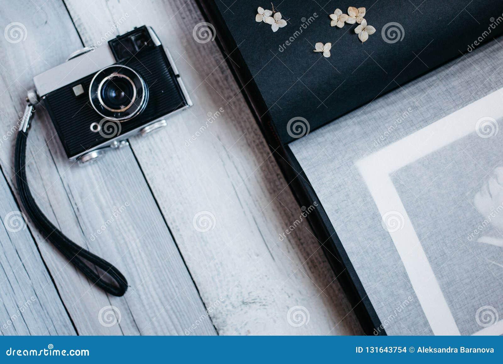 Tappningkamera, ett gammalt fotoalbum på den vita trätabellen