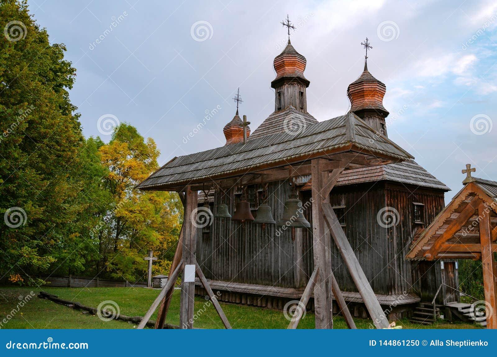 Tappningklockor på bakgrunden av en träkristen kyrka
