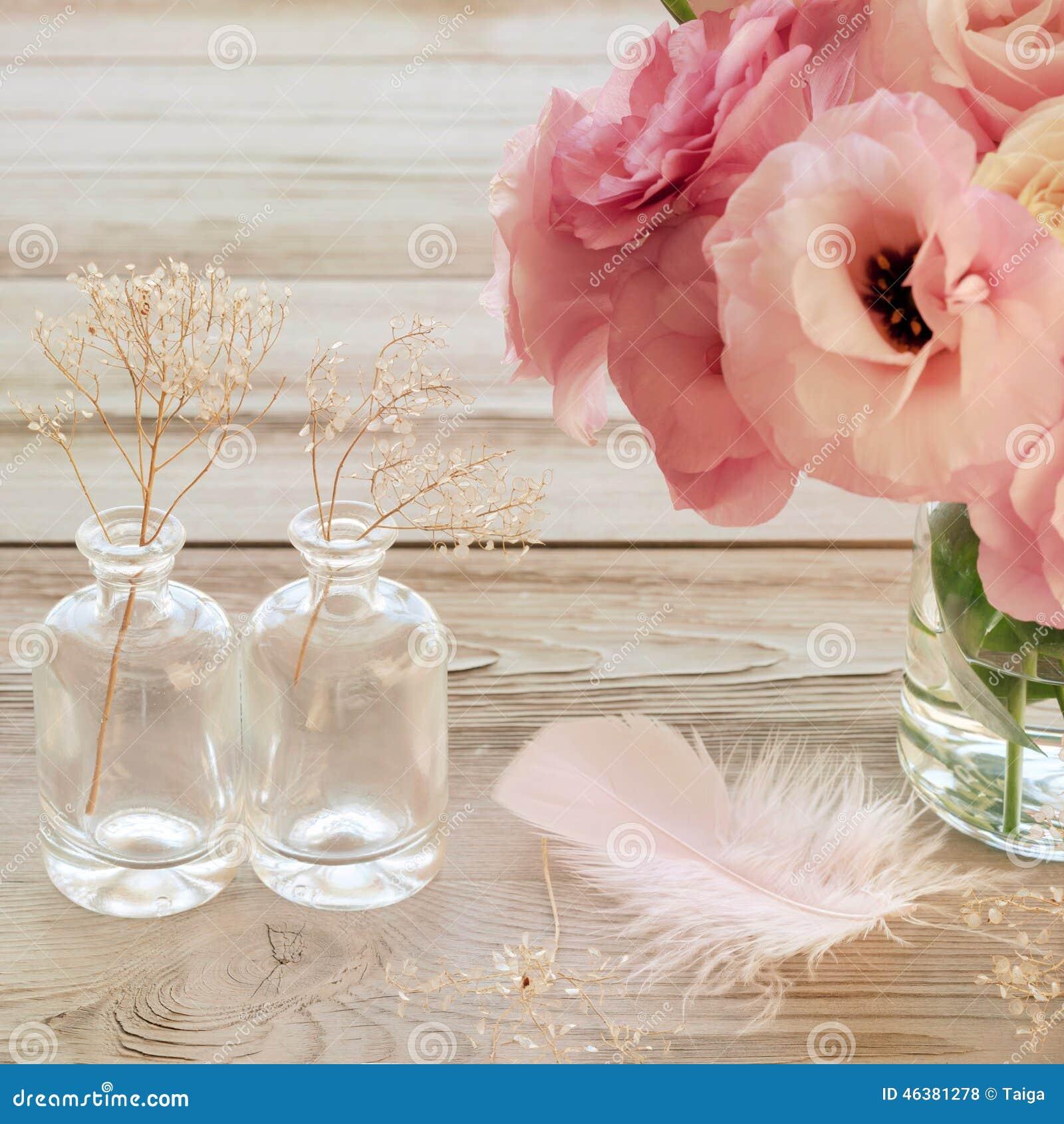 Tappningstilleben med rosa färger blommar i en vas med fearher och
