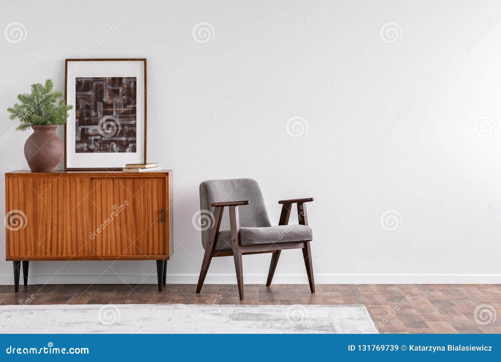 Tappningvardagsruminre med den retro möblemang och affischen, verkligt foto med kopieringsutrymme på den vita väggen