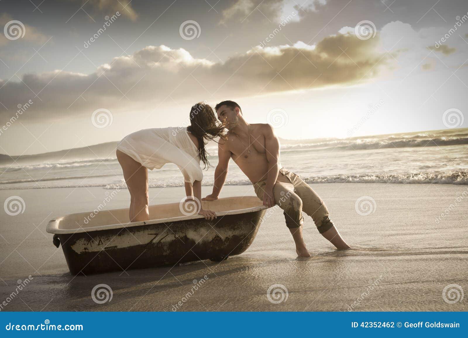Tarde hermosa joven del gasto de los pares en la playa con la tina de baño vieja