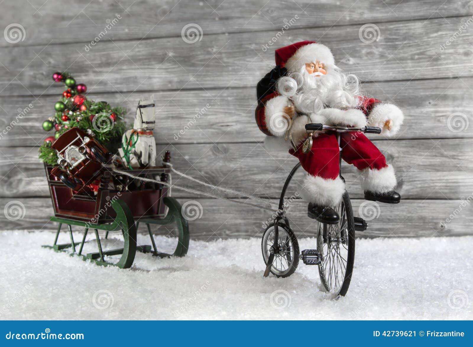 Tarjeta de felicitación divertida de la Navidad con Papá Noel en una bici que tira de un sli