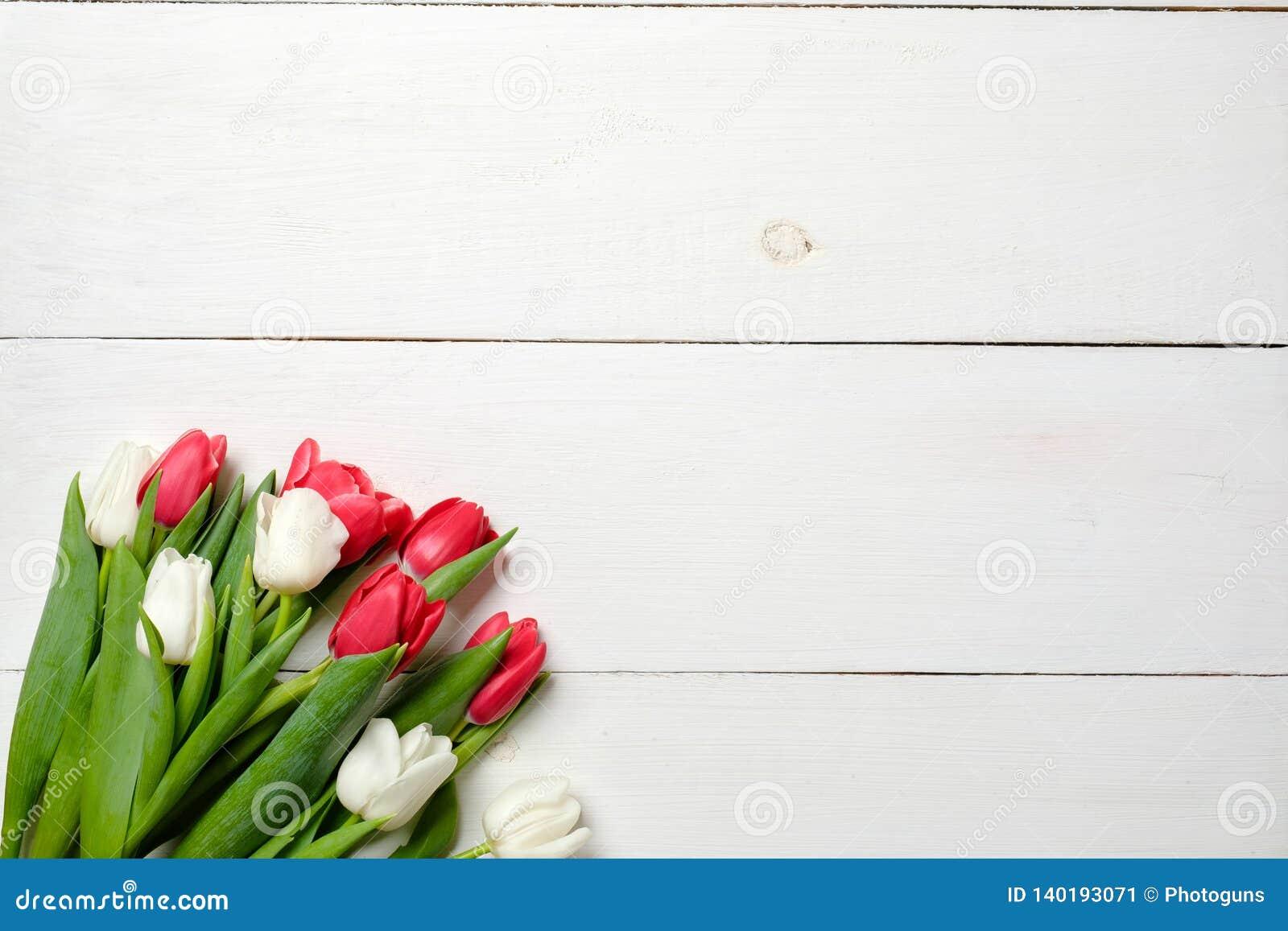 Tarjeta de felicitación en blanco con las flores de los tulipanes en la tabla de madera blanca Invitación de boda romántica, tarj