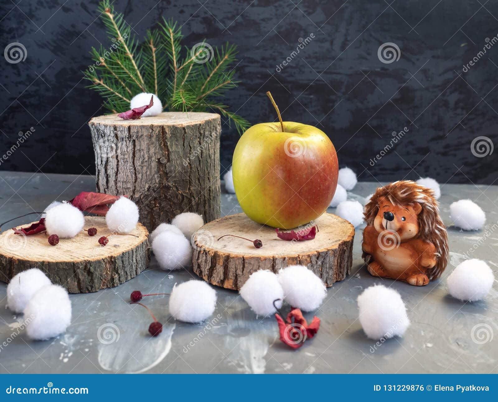 Tarjeta de Navidad El erizo encontró una manzana grande en el cáñamo del bosque Bolas de nieve, hojas de otoño secas