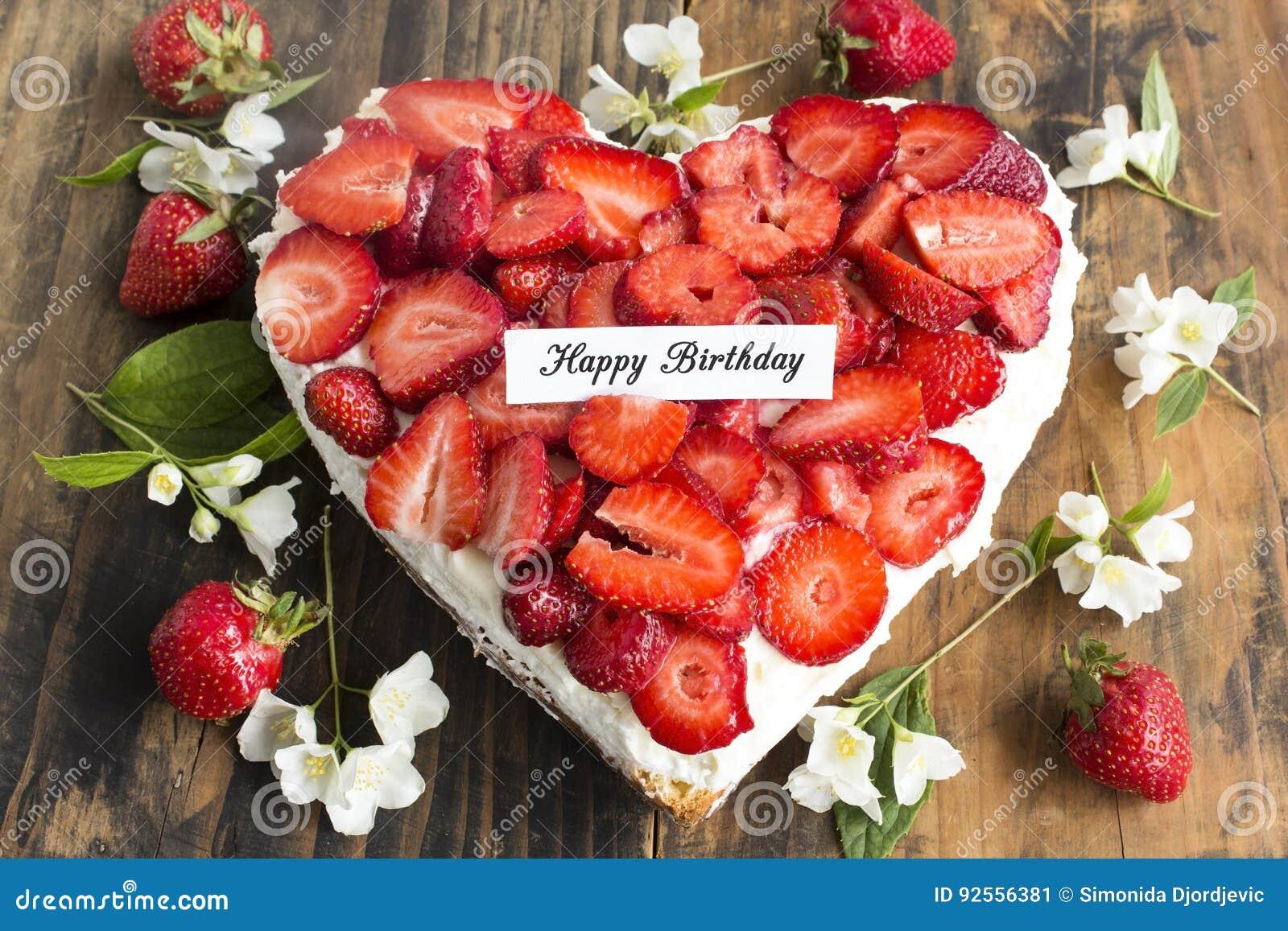 Tarjeta del feliz cumpleaños con el pastel de queso del corazón con las fresas