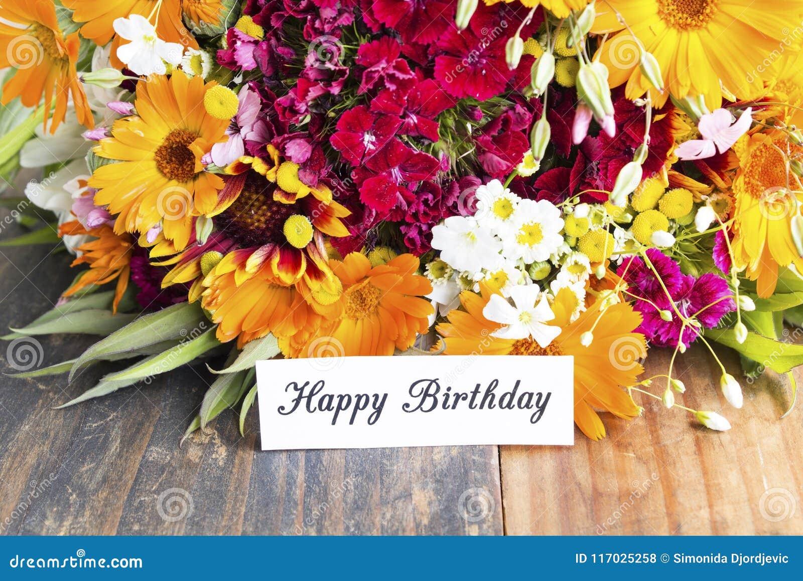 Tarjeta del feliz cumpleaños con las flores de la primavera
