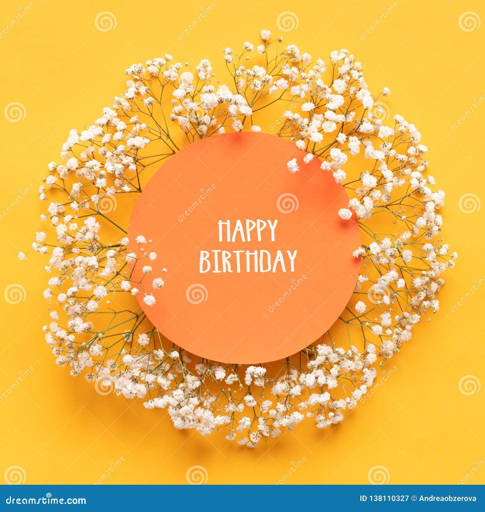Tarjeta del feliz cumpleaños Tarjeta de felicitación puesta plana con las pequeñas flores blancas hermosas en fondo de papel amar