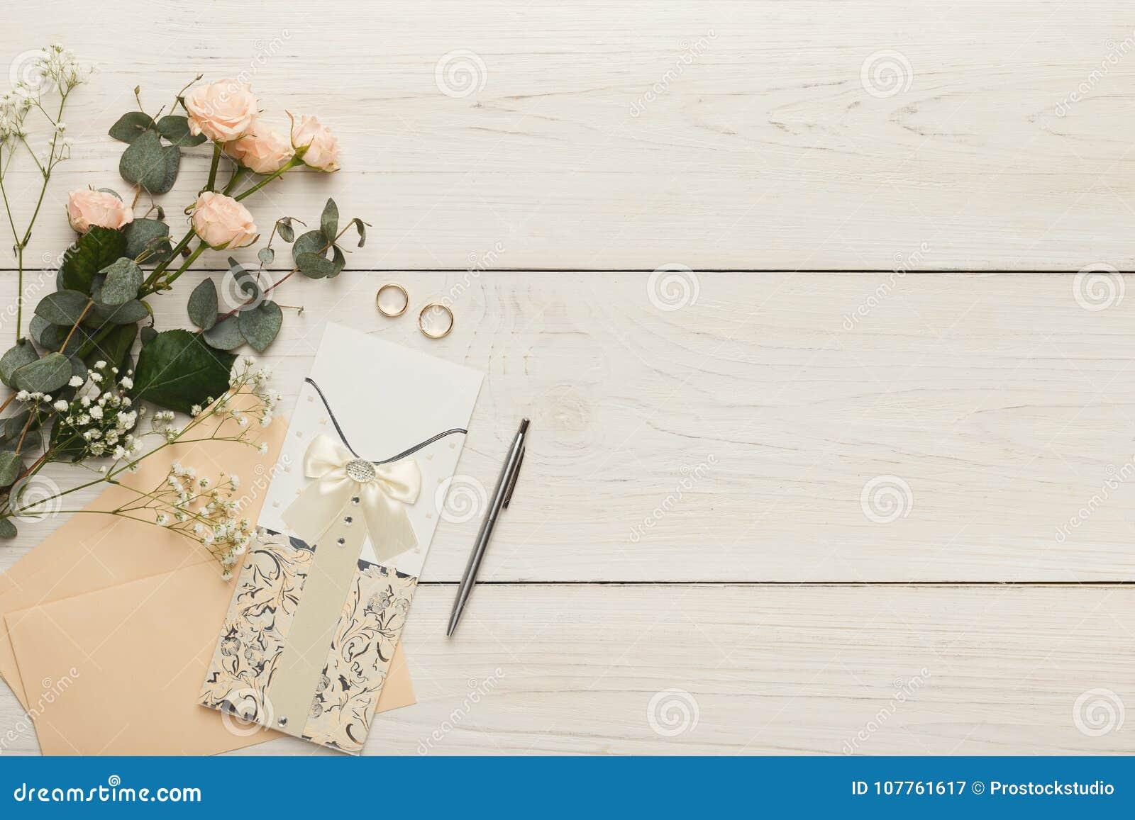 29e9c654342 Invitaciones de la boda y sobres del arte en el fondo de madera blanco  Opinión superior sobre las tarjetas de papel, los anillos y el ramo rosado  de las ...