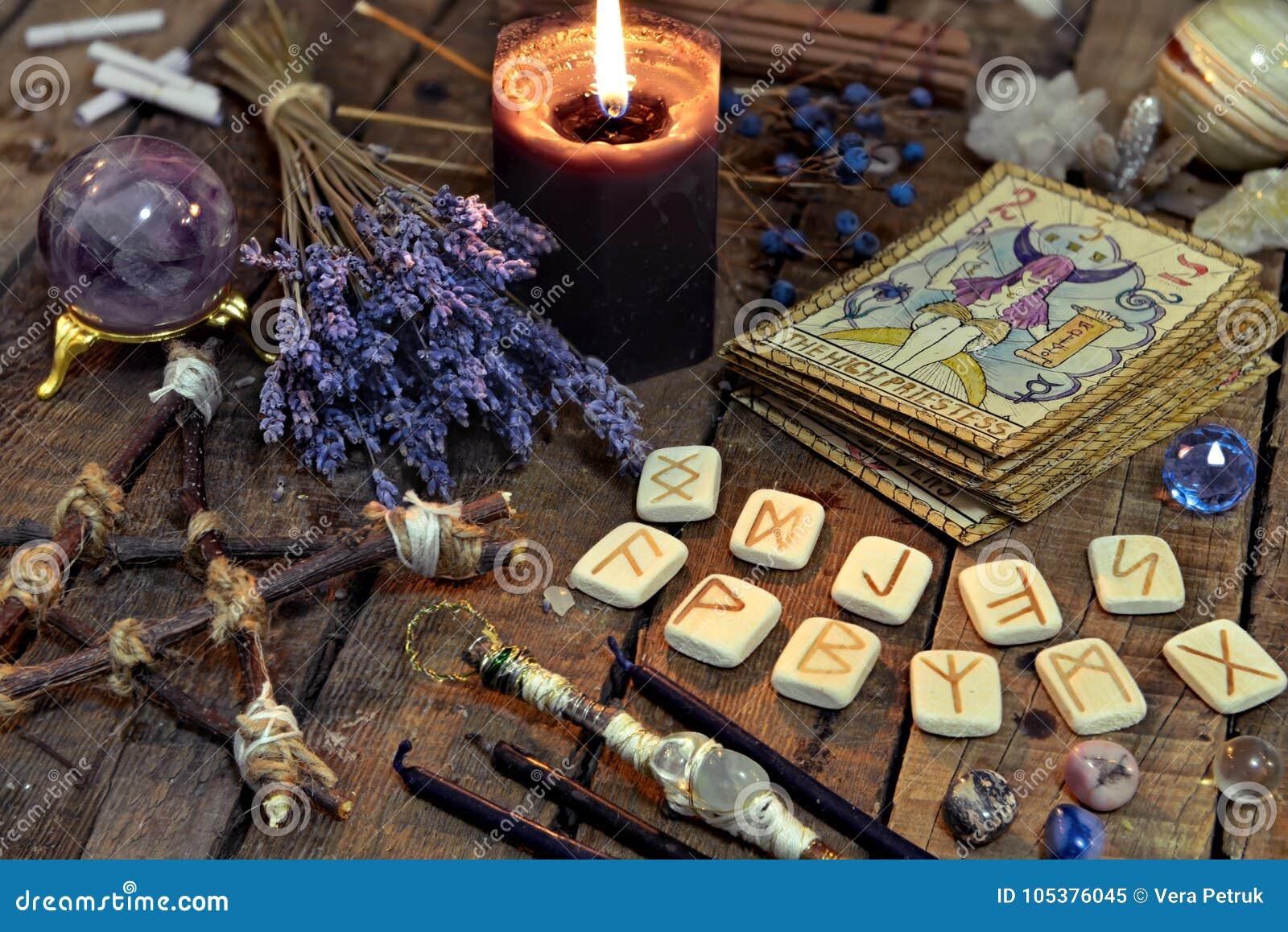Tarockkarten, alte Runen, schwarze Kerze und Pentagram