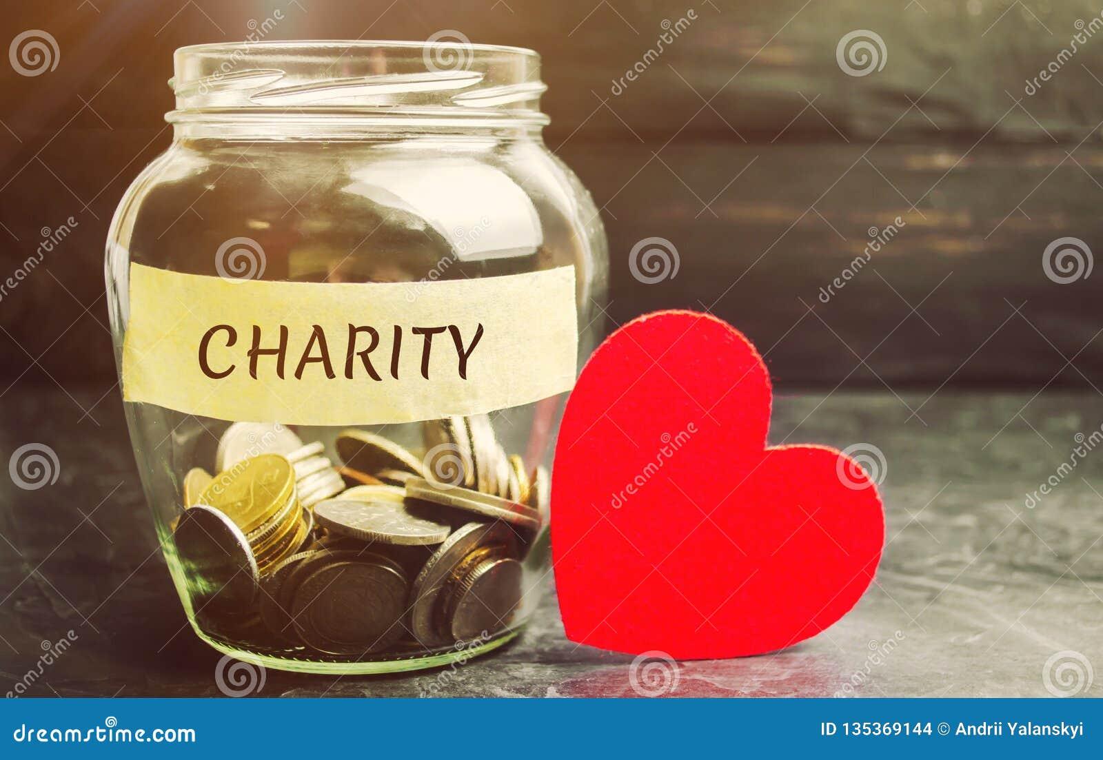 Tarro de cristal con la caridad de las palabras y el corazón El concepto de acumular el dinero para las donaciones ahorro Ayuda m