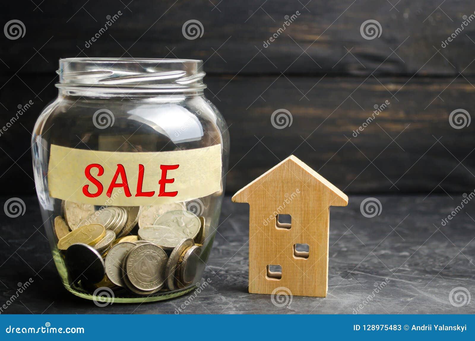 Tarro de cristal con las monedas y el ` de la venta del ` de la inscripción y una pequeña casa de madera Concepto 6 de las propie