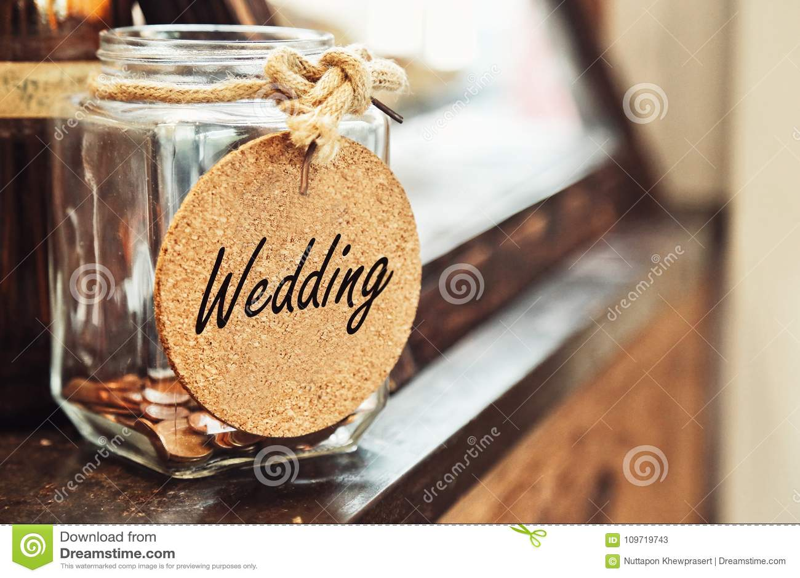 Tarro de cristal retro del vintage con la etiqueta de la boda del lazo de la cuerda del cáñamo y pocas monedas dentro en el conce