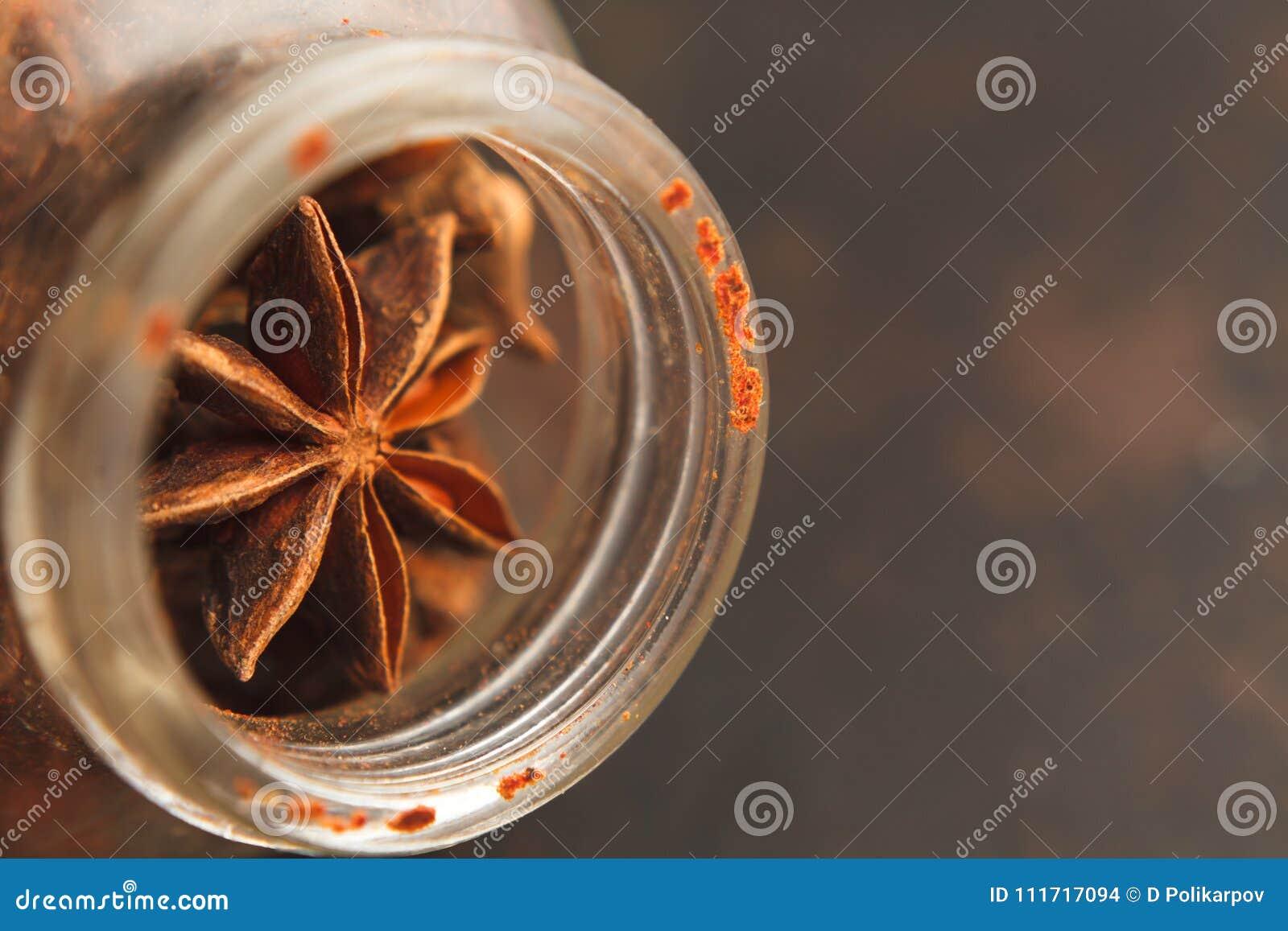 Tarro de cristal viejo con las semillas del anís de estrella en un fondo oscuro
