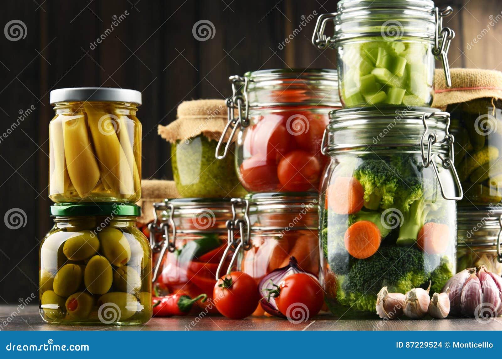 Tarros con la comida adobada y las verduras crudas orgánicas