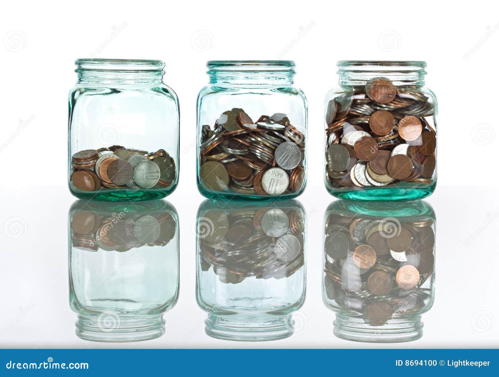 Tarros de cristal con las monedas - concepto de los ahorros