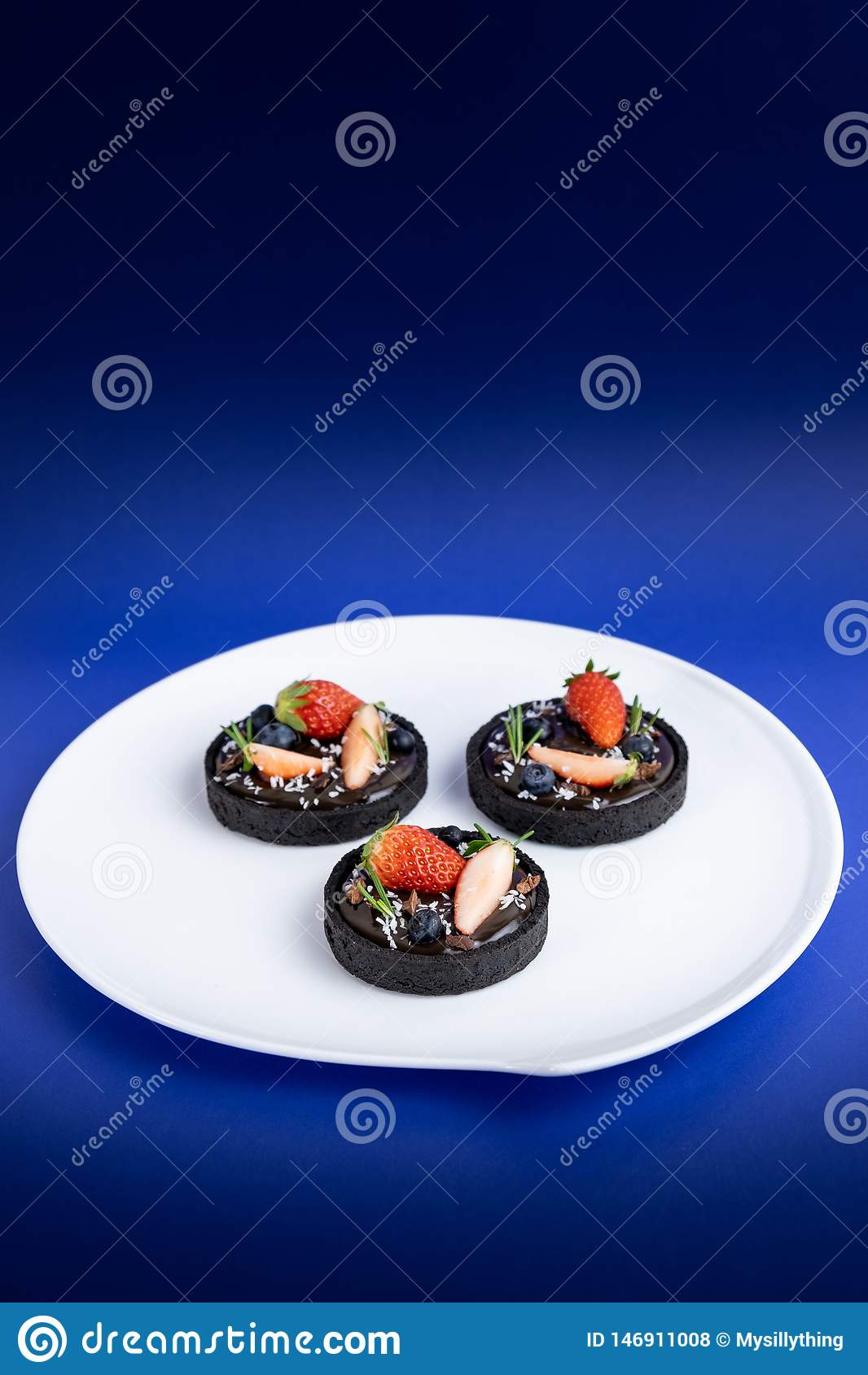 Tarta del chocolate de la corteza de la galleta con el sistema del ar?ndano y de la fresa en fondo azul