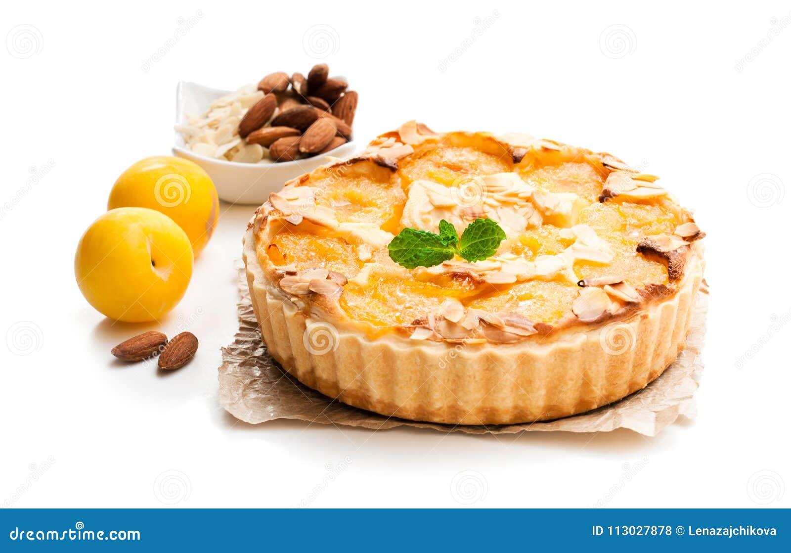 Tarta deliciosa con el ciruelo amarillo y las almendras aislados en blanco