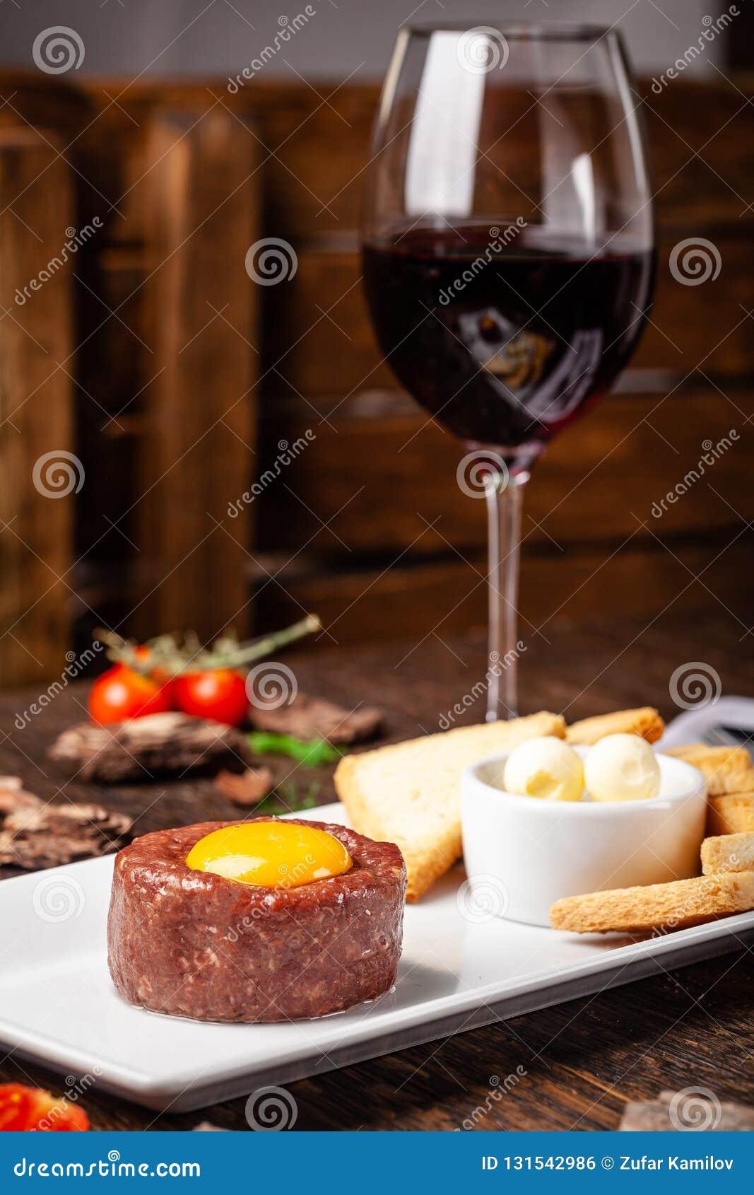 Tartare da carne crua da carne com especiarias e molhos diferentes separadamente para misturar Um vidro do vinho tinto na tabela