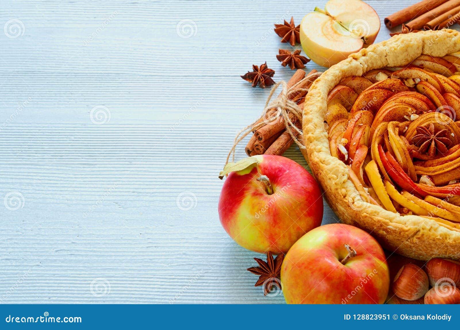 Tarte aux pommes d automne sur le conseil en bois décoré des pommes fraîches, noisettes, épices - anis, cannelle sur la table de