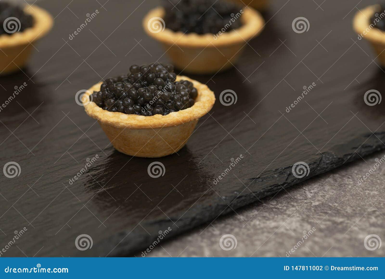 Tartlets com fim preto do caviar acima Fim do alimento gourmet acima, aperitivo delicatessen Alimento do gourmet Textura do cavia