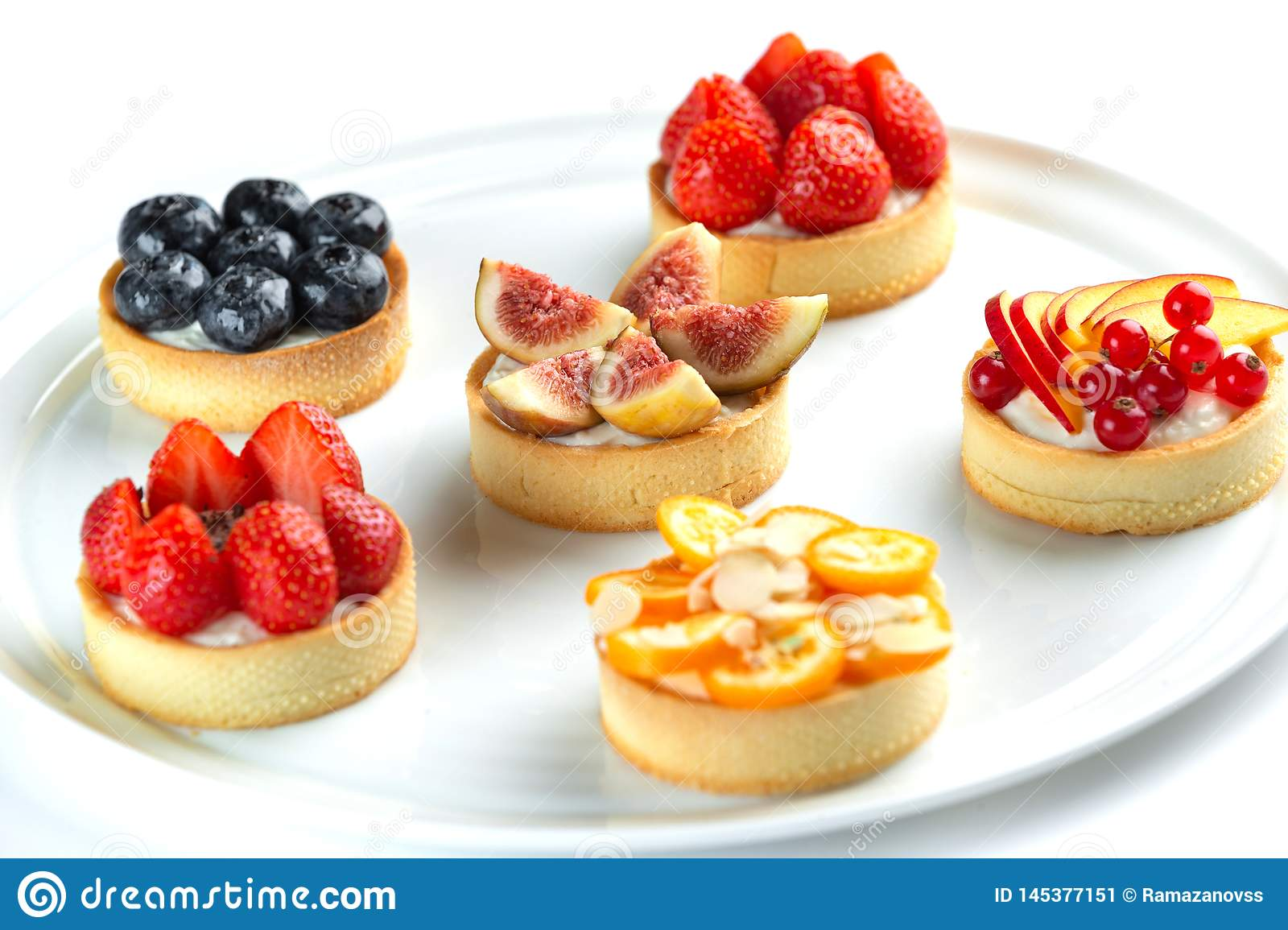 tartlets with fruits and berries on an isolated white background