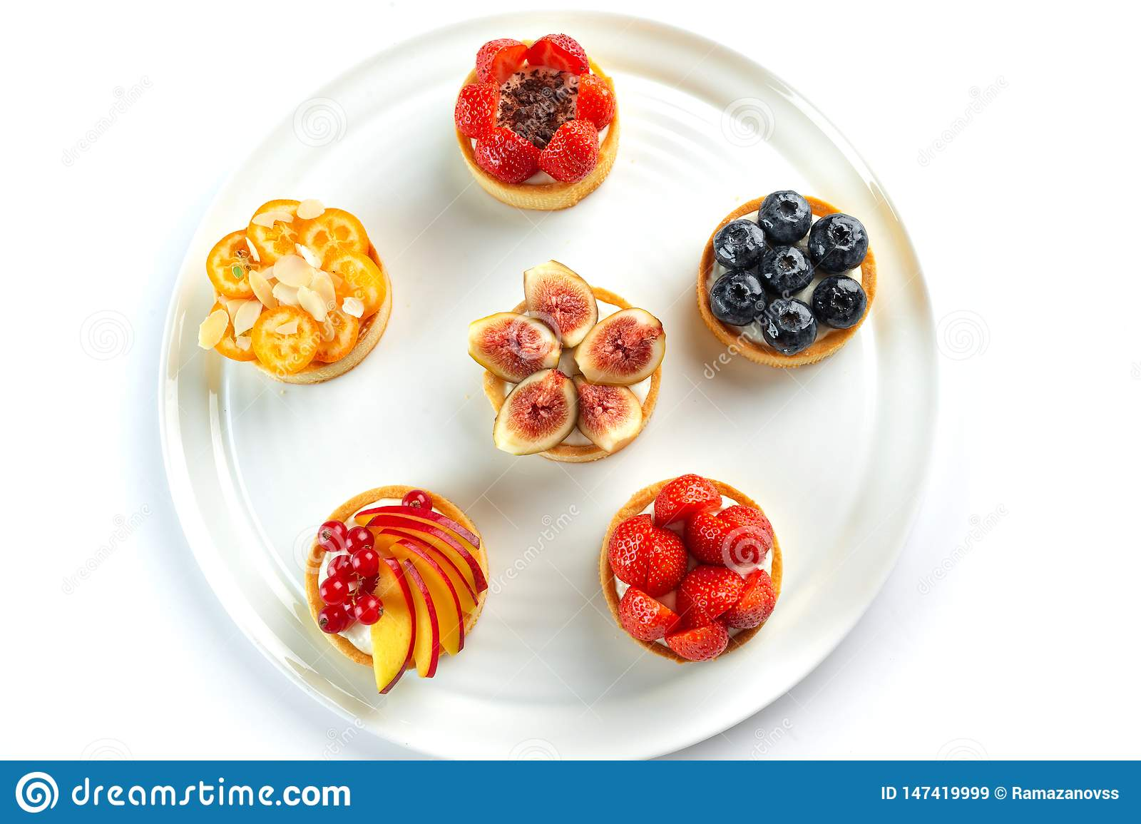 Tartlets with fruits and berries in a round plate on an isolated white background