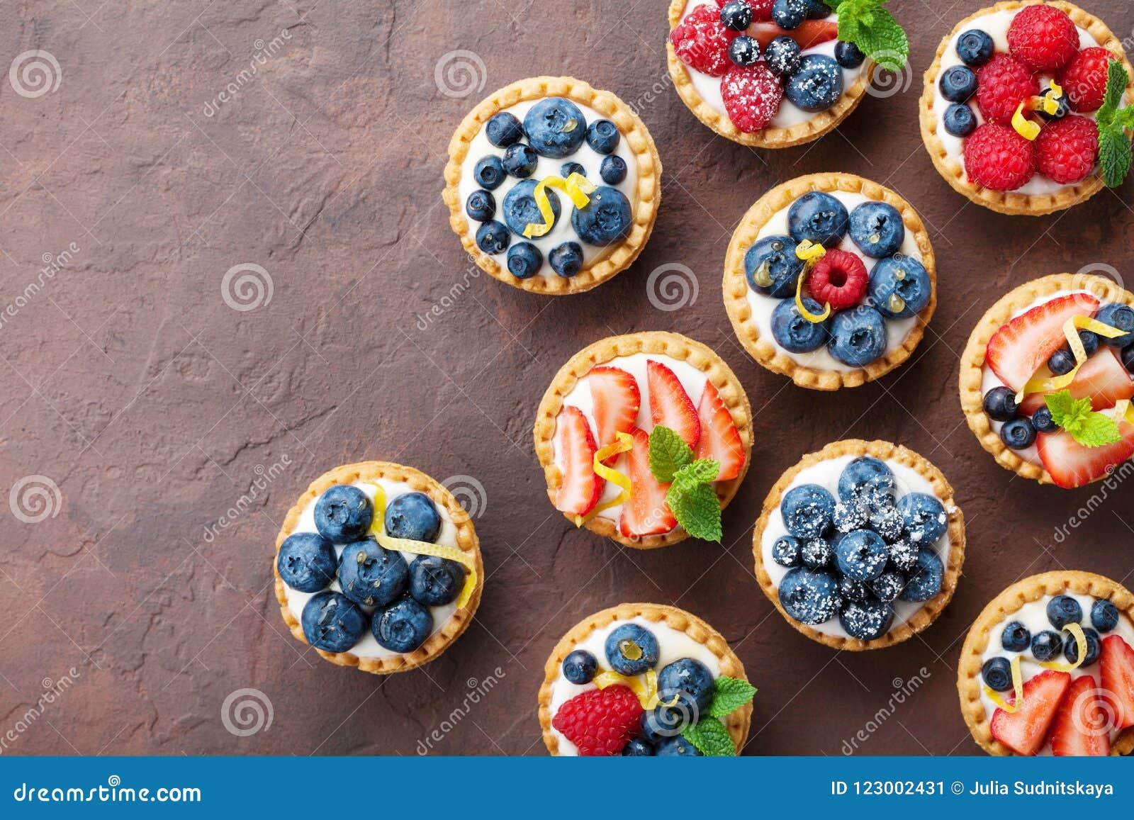 Tartlets o torta del verano con la opinión superior del queso cremoso y de la baya mezclada Postres sabrosos de los pasteles