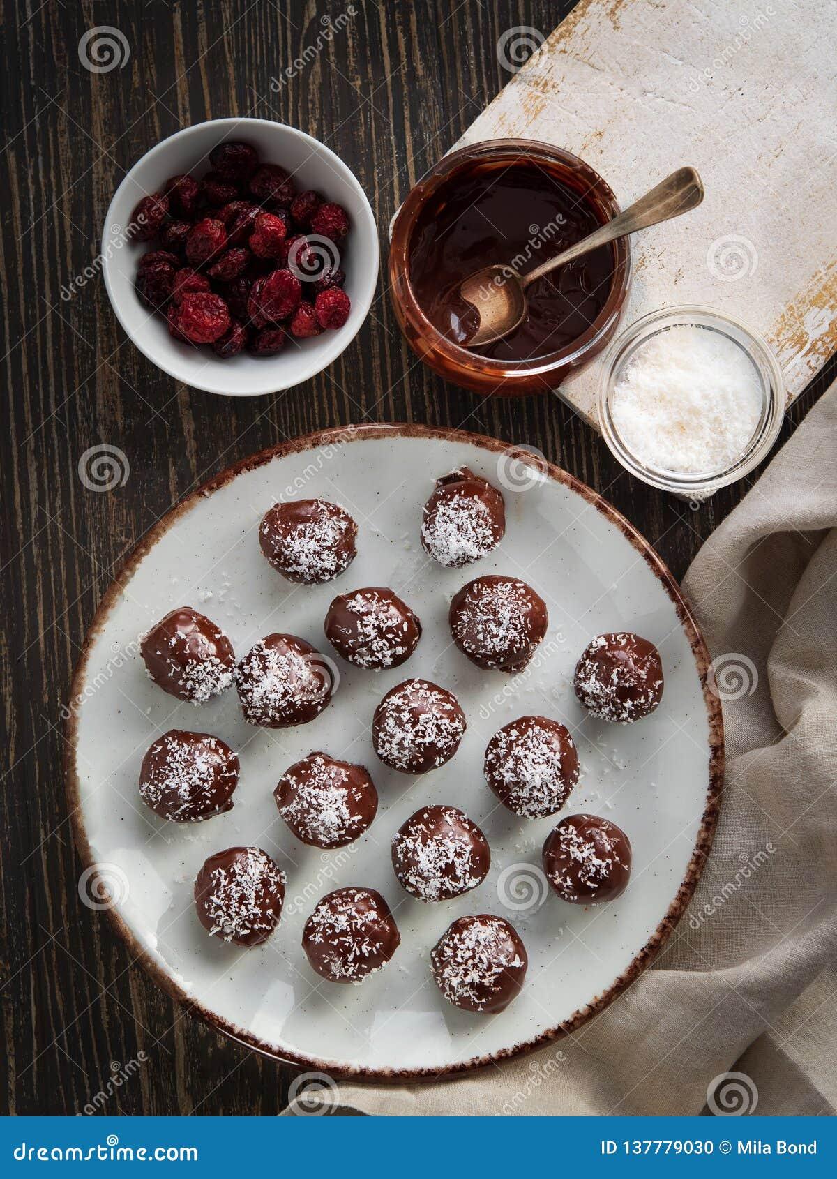 Tartufi di cioccolato sani con i dadi, i datteri, i mirtilli rossi secchi ed i fiocchi della noce di cocco su fondo rustico Vista
