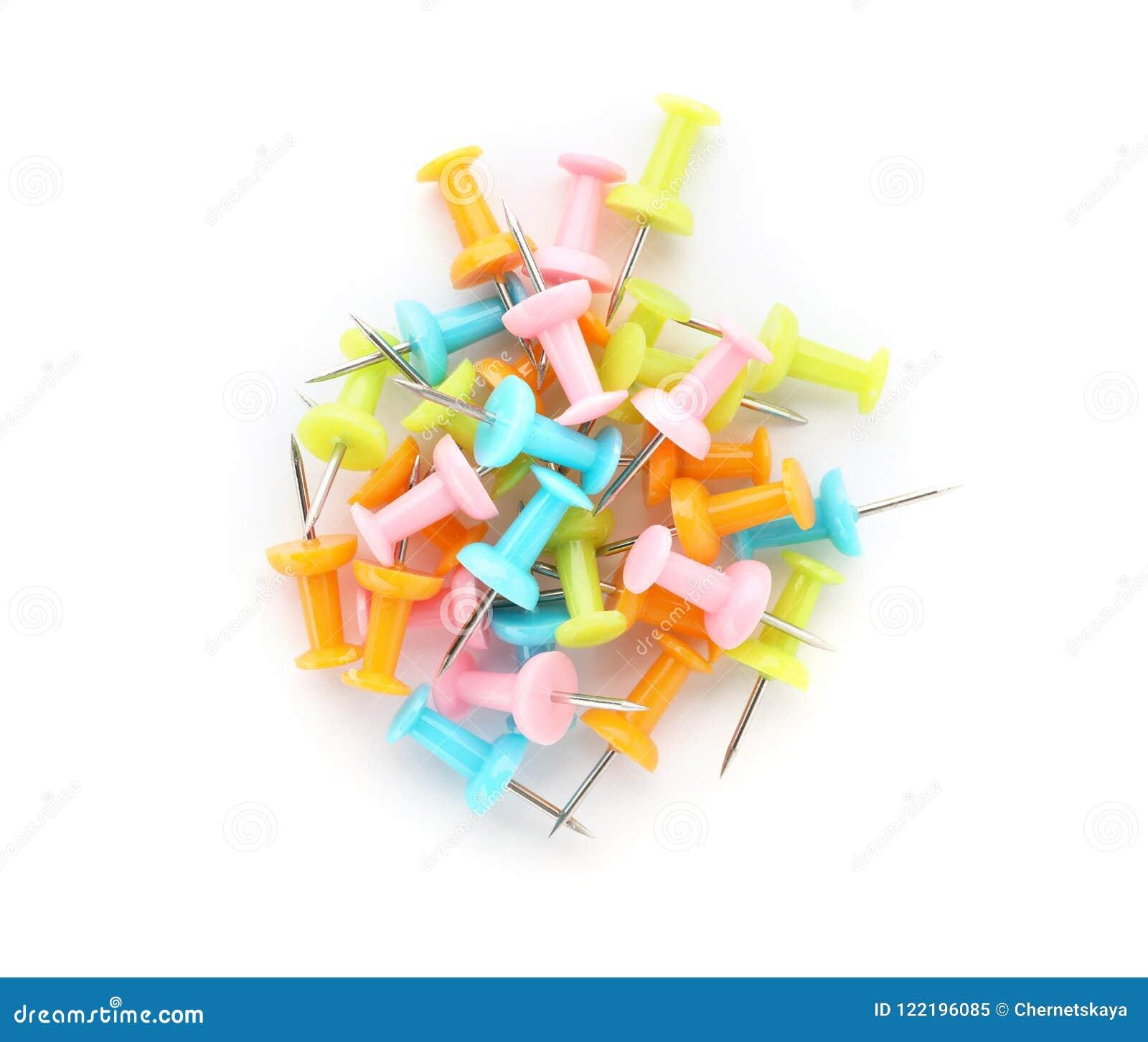 Tas des goupilles colorées de poussée sur le fond blanc
