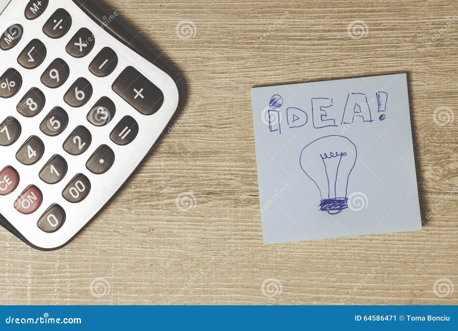 Taschenrechner und blaues Post-It auf dem Schreibtisch