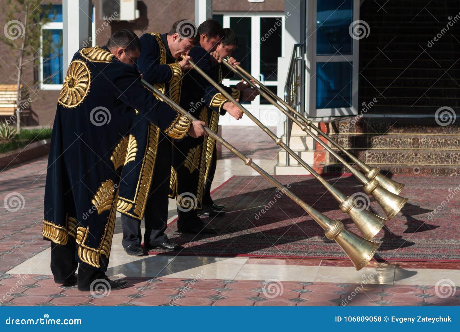TASHKENT UZBEKISTÁN - 9 de diciembre de 2011: Hombres del músico en los kaftans tradicionales que juegan el karnay