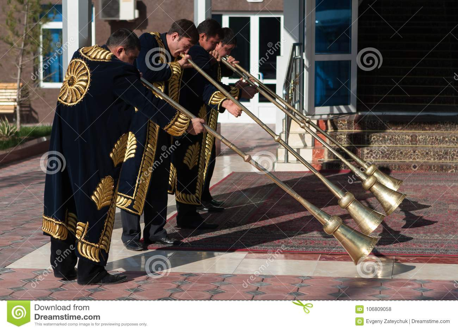 TASHKENT UZBEKISTAN, Grudzień 9 2011 -: Muzyków mężczyzna w tradycyjnych kaftans bawić się karnay