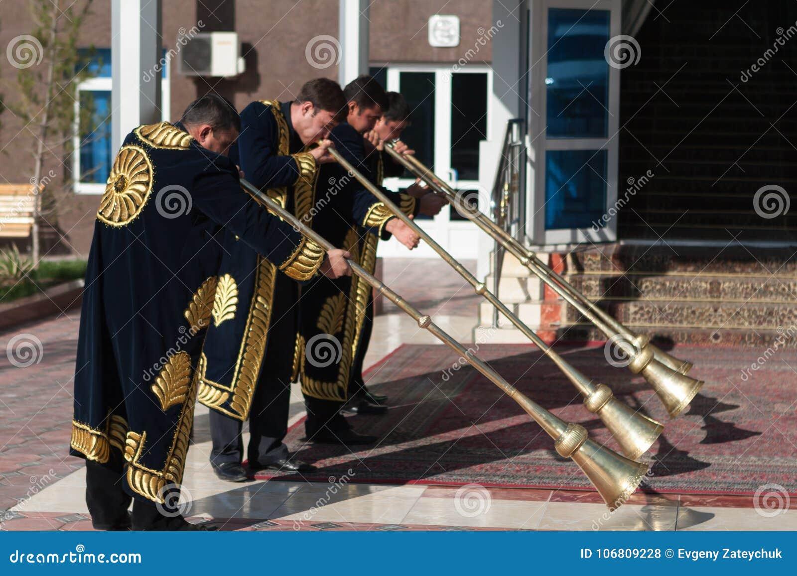 TASJKENT UZBEKISTAN - December 9 2011: Musikermän i traditionella kaftans som spelar det karnay