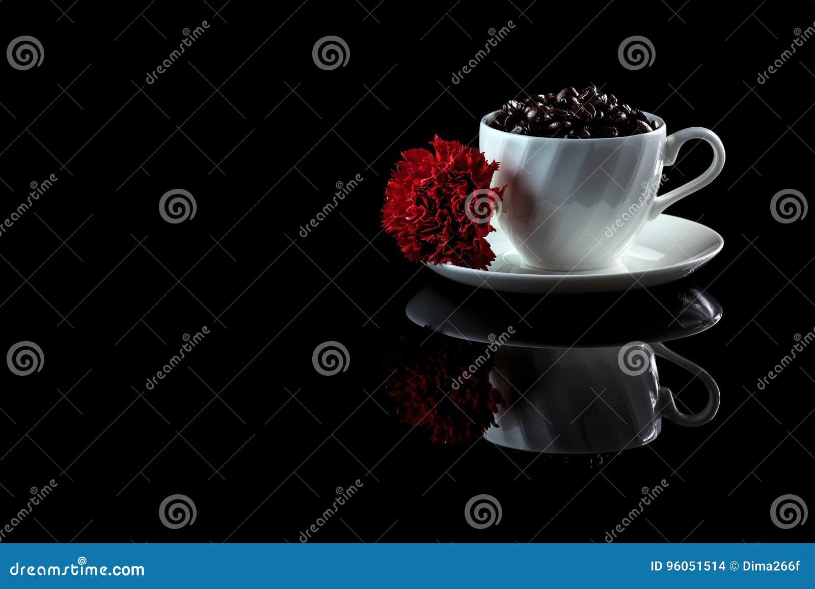 Tasse avec des grains de café et oeillet rouge sur un CCB réfléchi noir