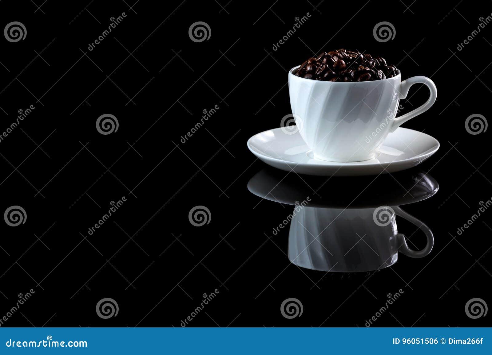 Tasse avec des grains de café sur un fond réfléchi noir
