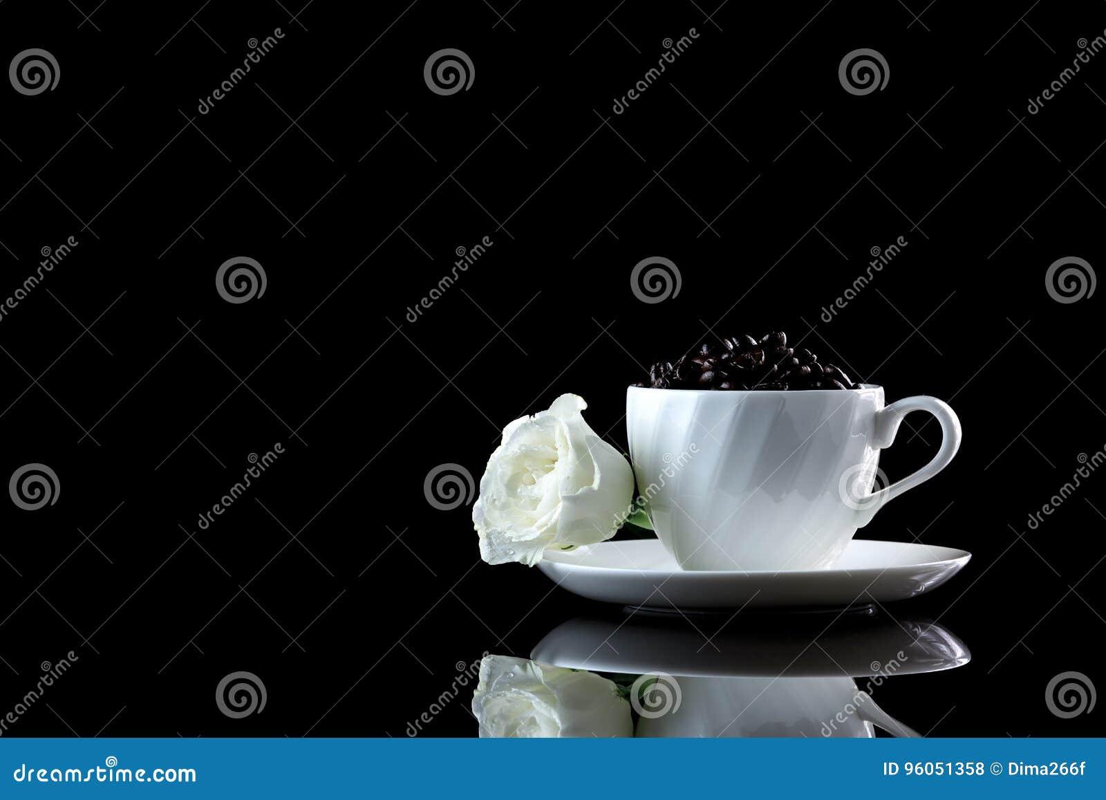 Tasse avec les grains de café et la rose de blanc sur un backgr réfléchi noir