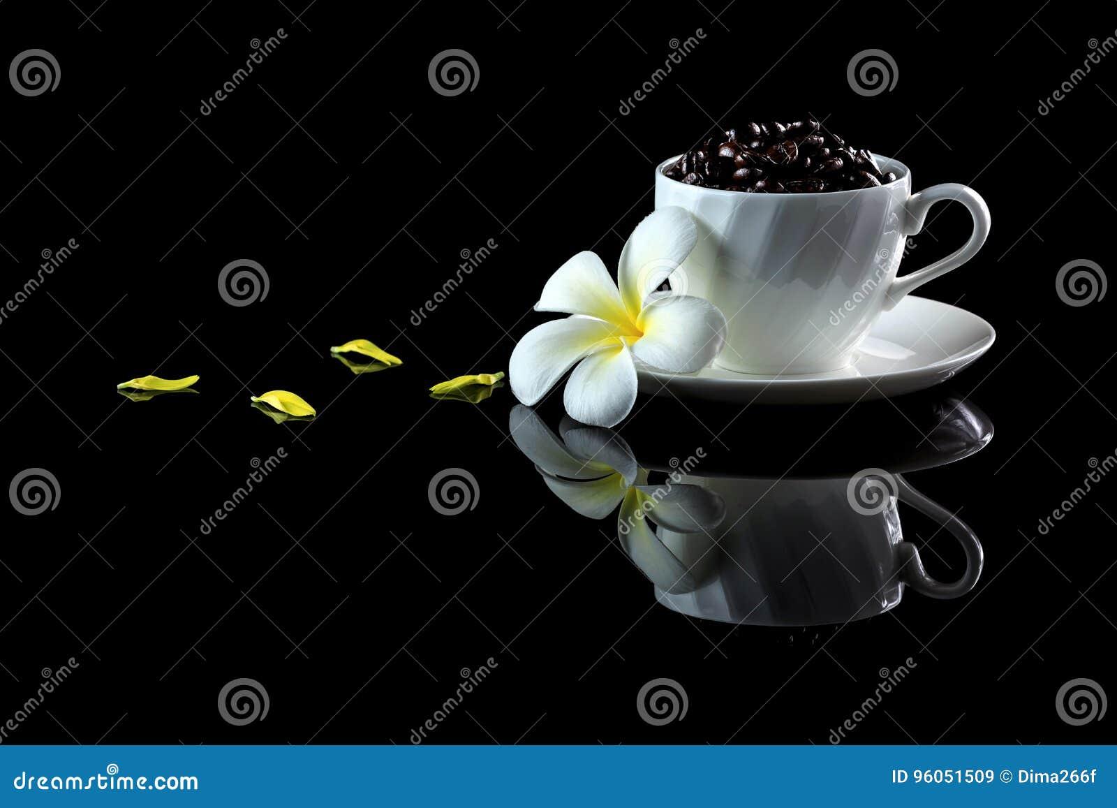Tasse avec les grains de café et le frangipani sur un backgr réfléchi noir