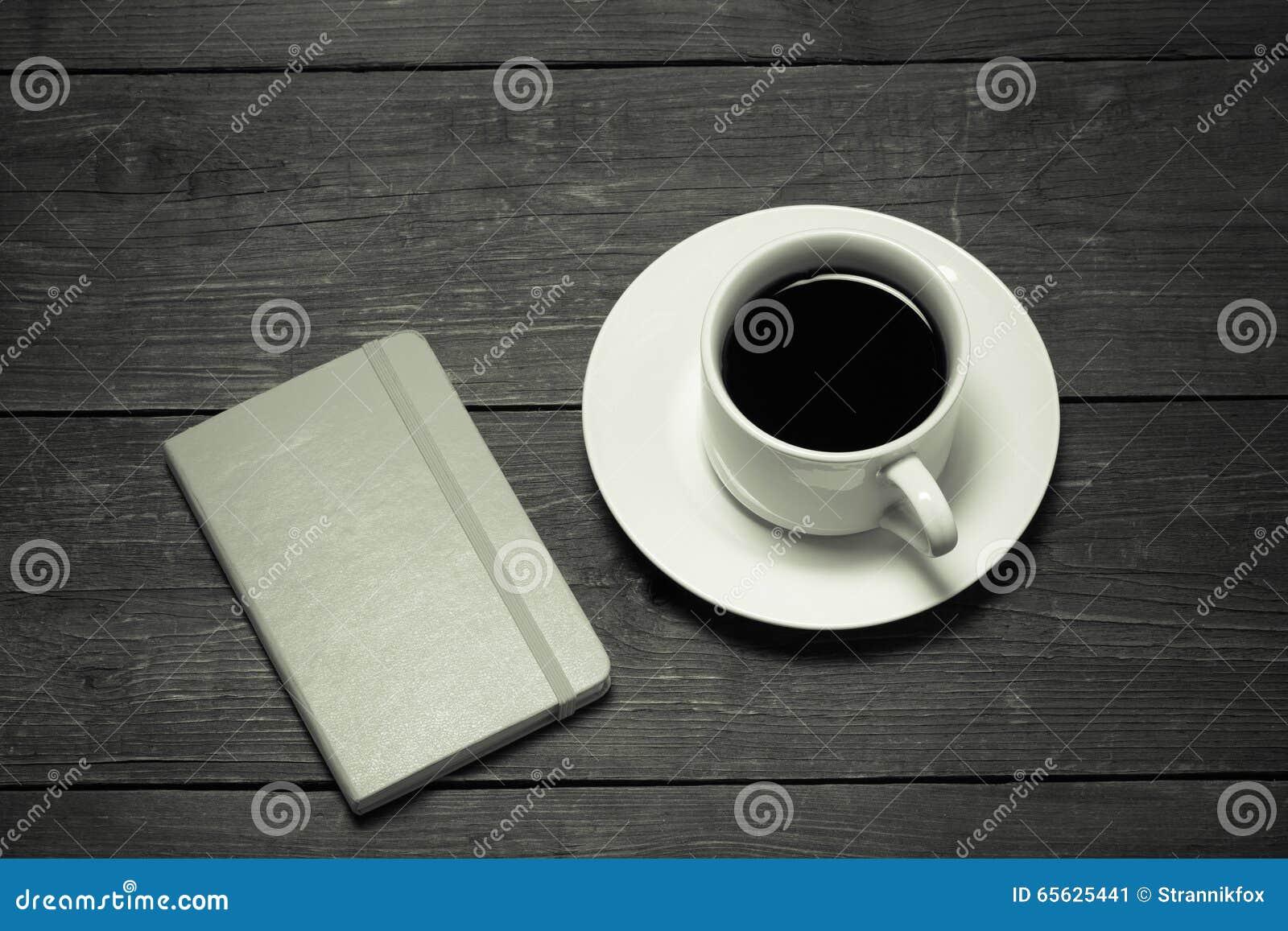 Tasse blanche de café et de carnet sur la vieille table en bois toned
