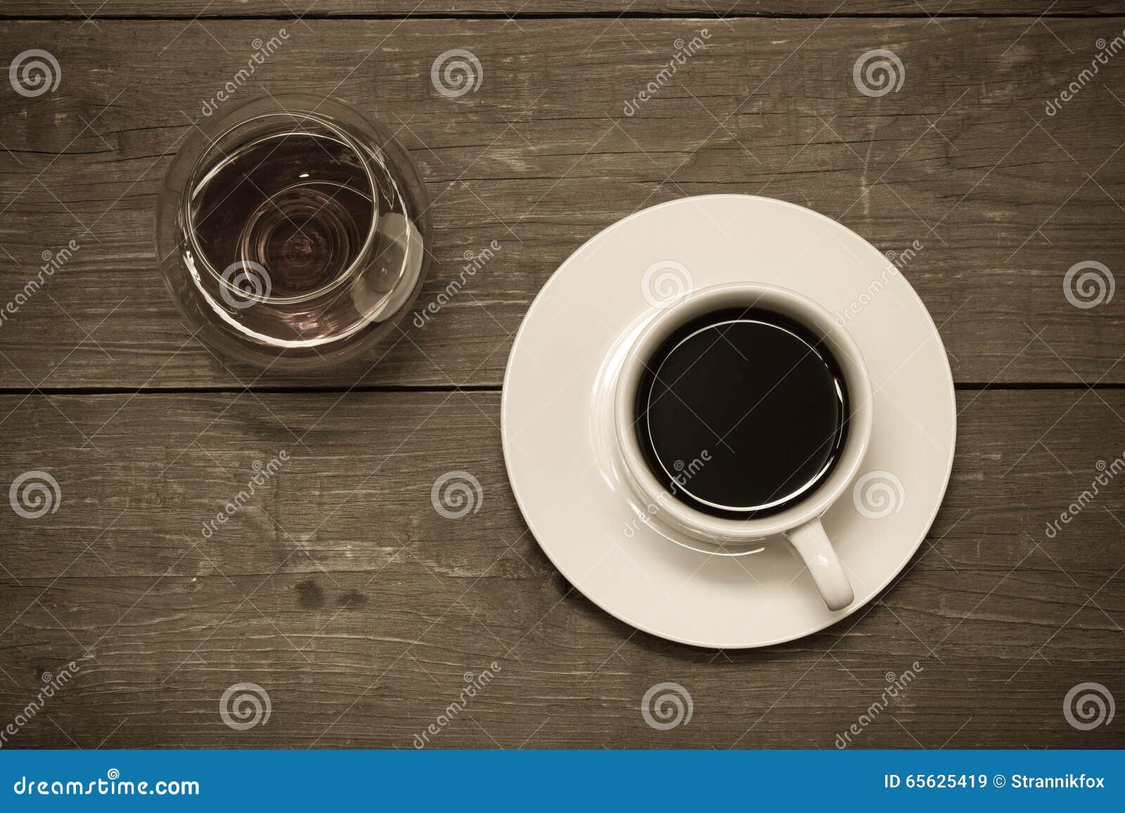 Tasse blanche de café et de cognac dans un verre sur la vieille table en bois T