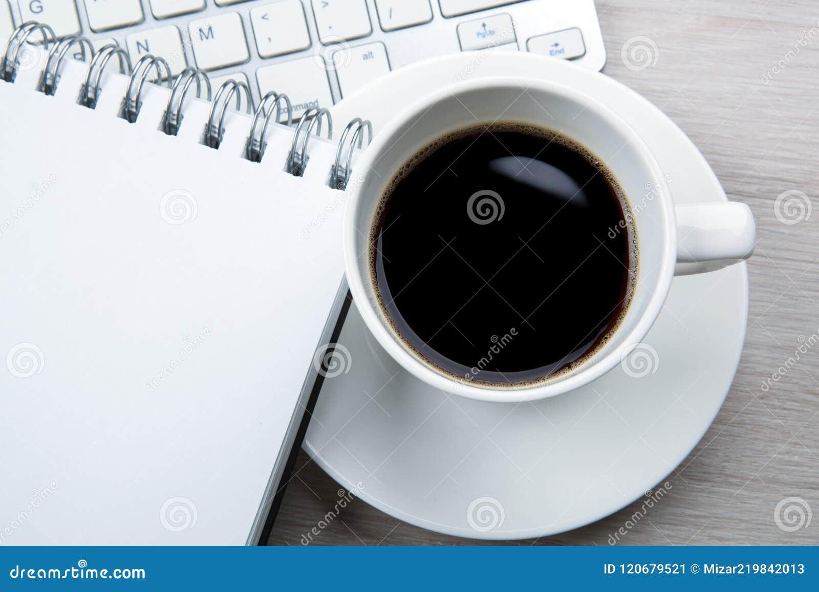 Tasse blanche de café noir avec la mousse bloc notes clavier sur