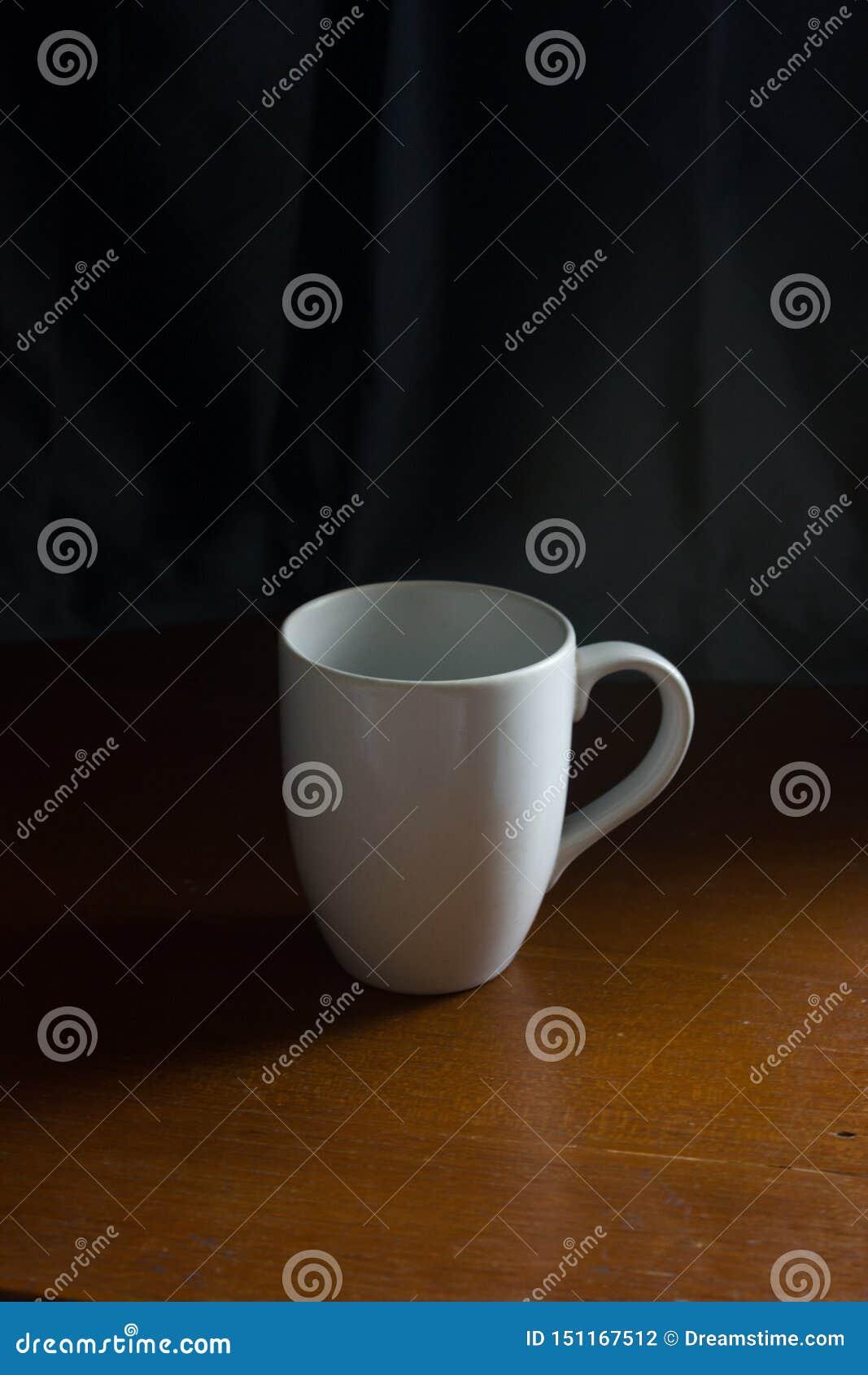Tasse blanche sur la table en bois avec le rideau bleu-foncé à l arrière-plan, détente de sensation, meilleure pour la maquette