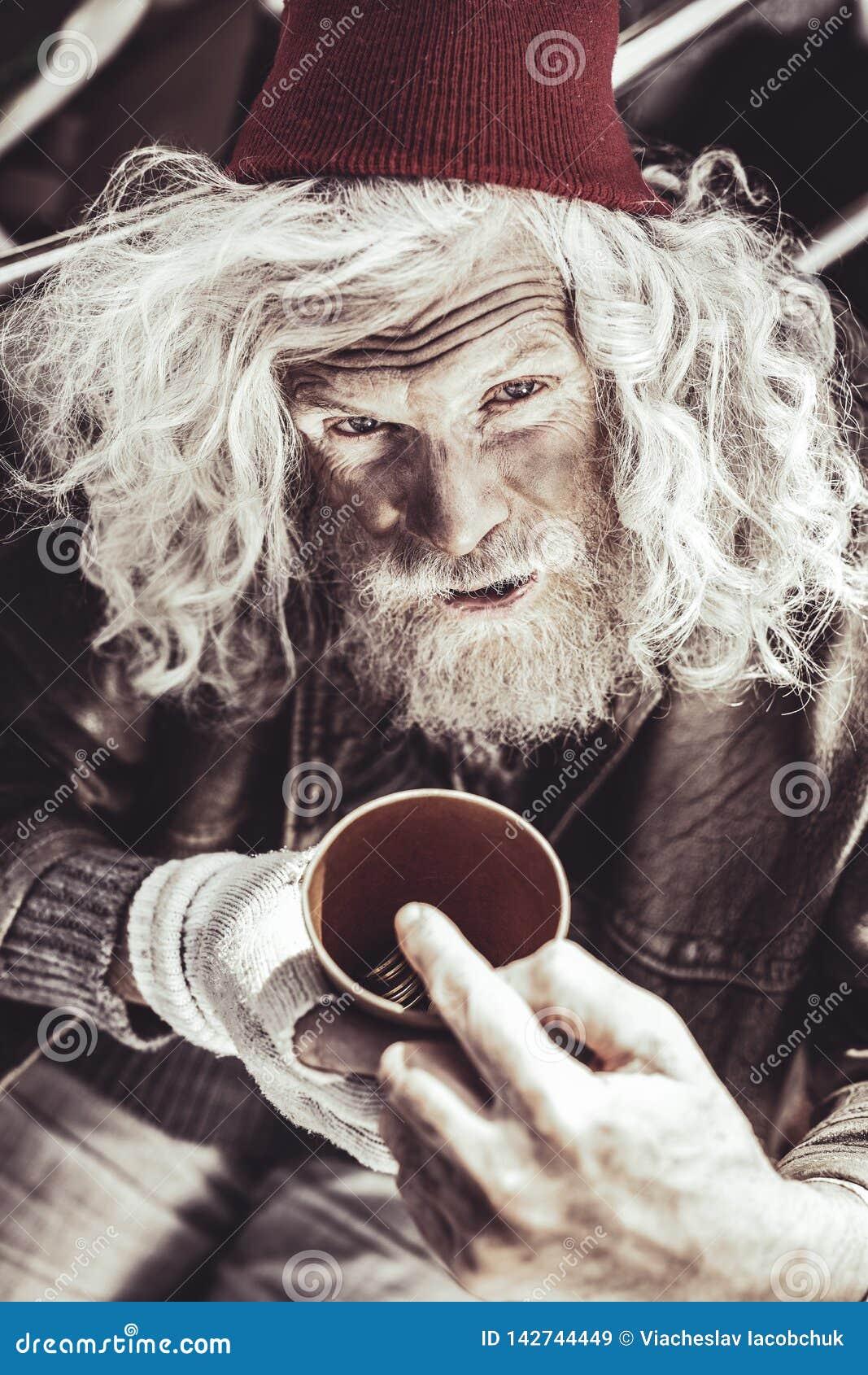 Tasse caucasienne de participation d almsman avec l argent et montrer son revenu quotidien