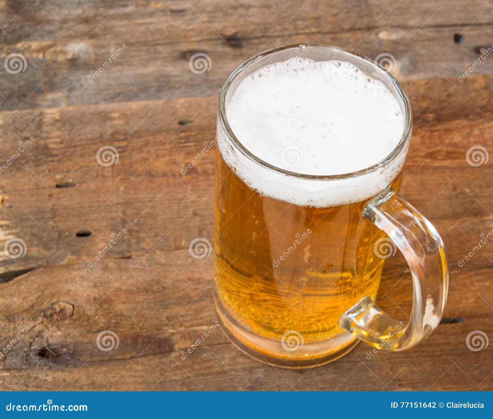 Tasse de bière blonde avec la mousse sur les panneaux en bois d un vintage foncé