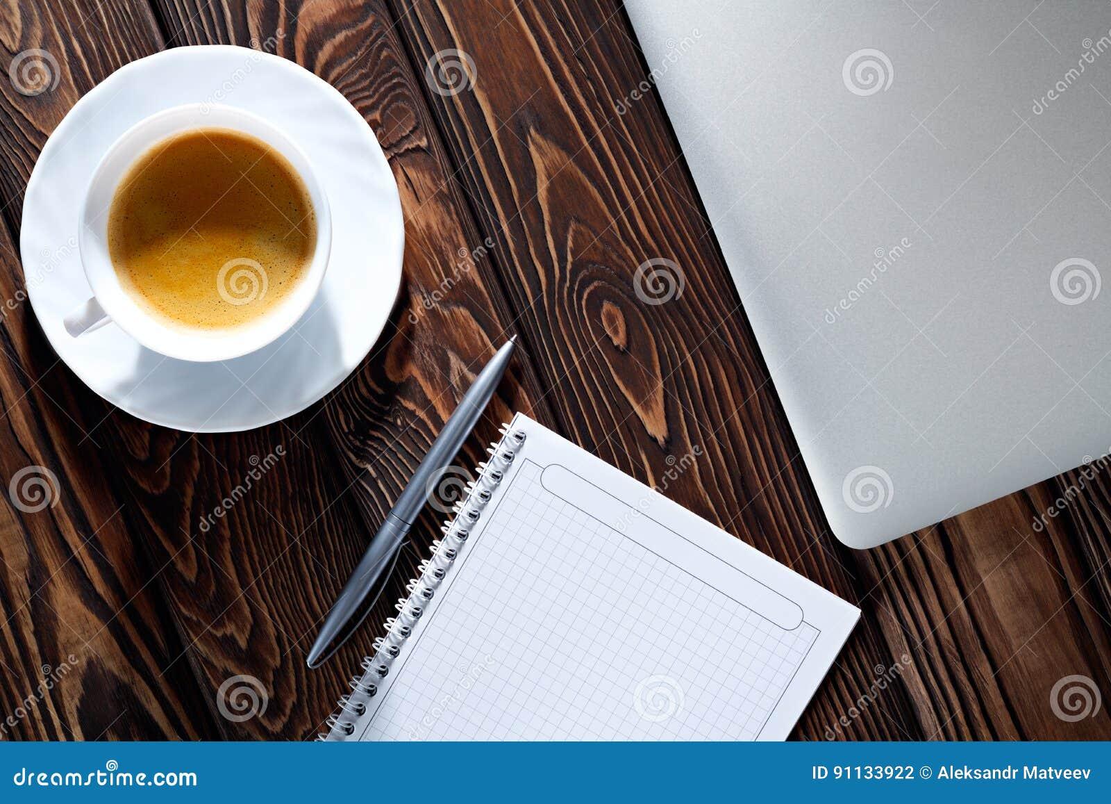 Tasse de bloc-notes, d ordinateur portable et de café sur la table en bois