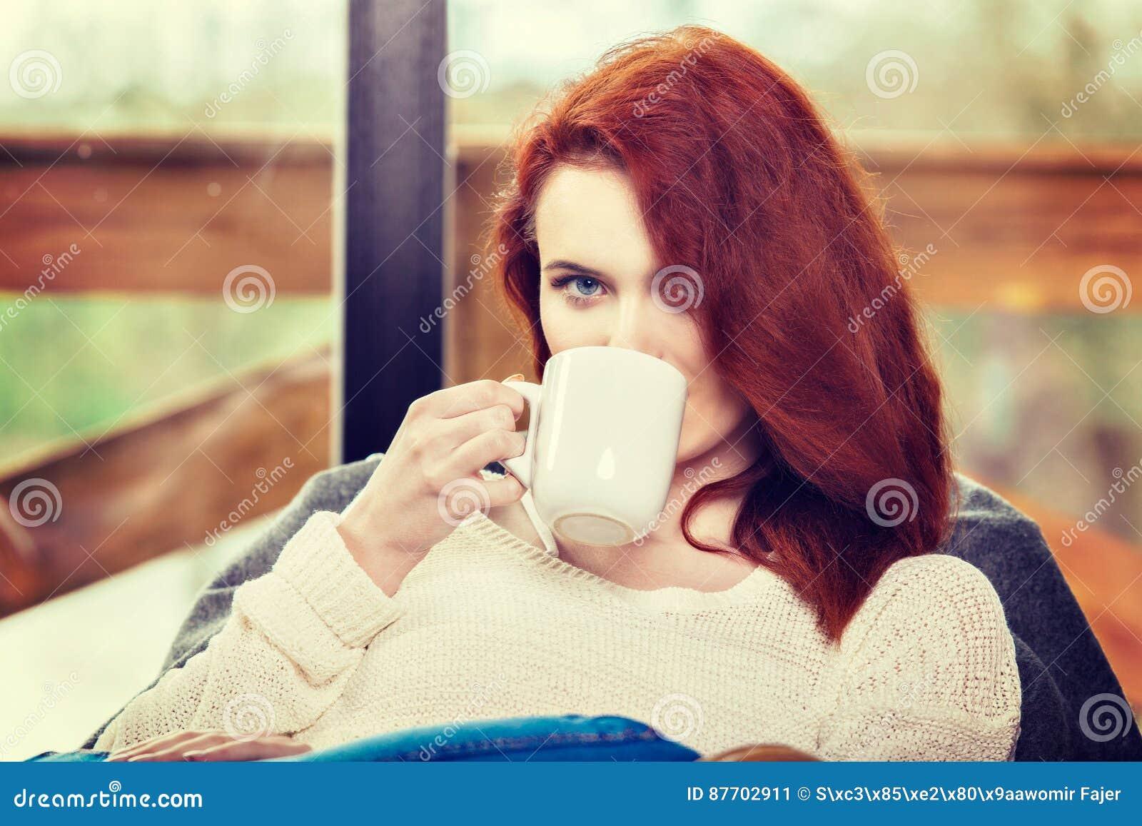 Tasse de boissons de femme d Atractive de café rousse se reposant sur la chaise de basculage Jeune fille avec la boisson de activ