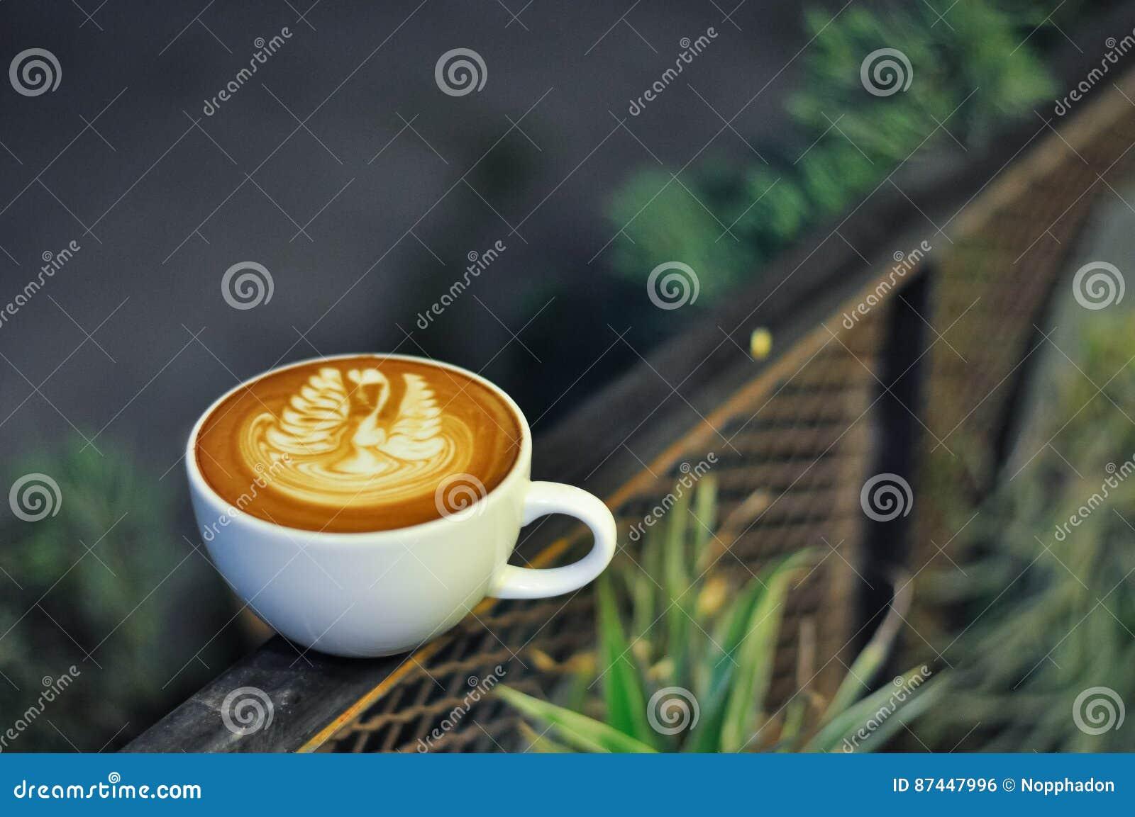 Tasse de café avec l art de latte sur la barrière en métal la nuit