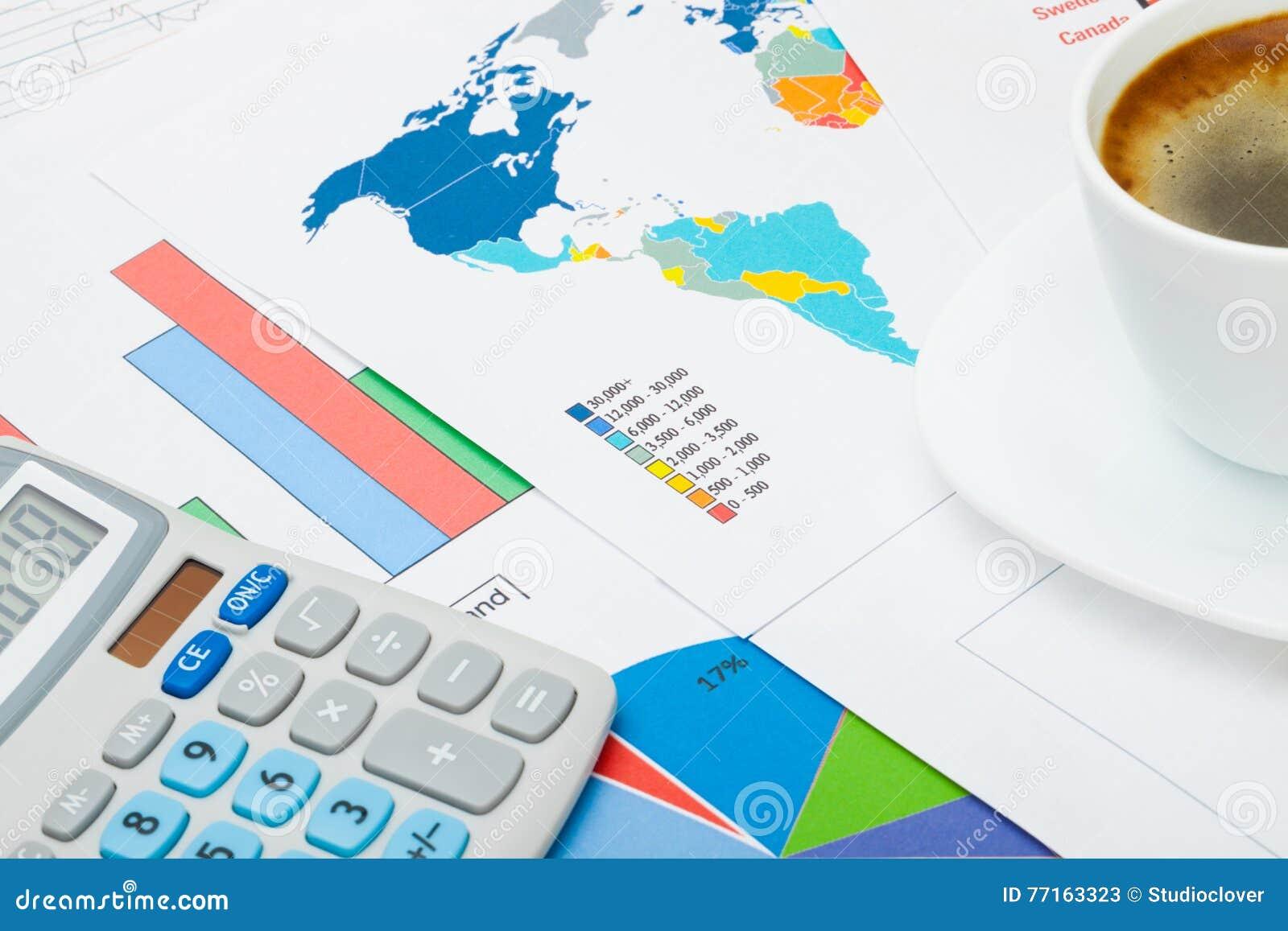 Tasse de café avec la calculatrice au-dessus de la carte du monde et de quelques diagrammes